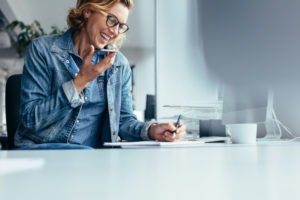 Woman working at her desk at home. She's writing and talking on the phone.